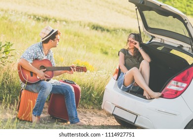 Young couple taking a break on their road trip. Summer vacation travel concept.