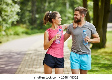 Young couple taking break while joging and embracing in the park