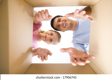 Young couple taking out something from cardboard box. They're looking at camera. Low angle view.