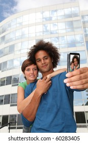 Young couple taking picture of itself with mobile phone