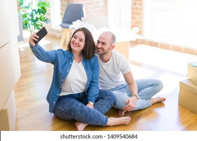 Young couple taking a picture photo using smartphone at new home, sitting on the floor smiling happy for moving to new apartment
