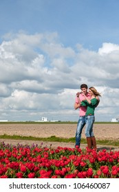 Young couple is taking pictures in Holland from flower fields