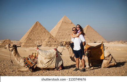 Young Couple taking posing for a photo in front of camels with the Great Pyramids of Giza in the background