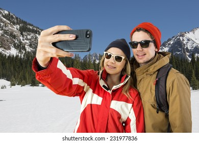 Young couple taking a selfie in front of a beautiful winter landscape during their wintersport