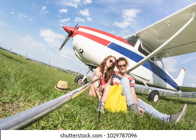 Young couple taking selfie at lightweight airplane - Happy people boarding on excursion air plane - Alternative adventure vacation concept - Warm day colors with tilted horizon fisheye distortion