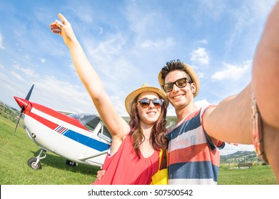 Young couple taking selfie with lightweight airplane - Happy people boarding on excursion air plane - Alternative adventure vacation concept - Warm day colors with tilted horizon fisheye distortion
