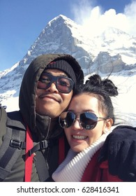 Young couple taking a selfie on snow mountain in Switzerland
