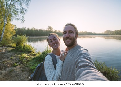 Young couple taking a selfie portrait by the lake shore at sunrise, sunbeam and reflection on water's surface. People travel love romance sharing.