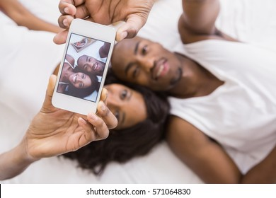 Young couple taking a selfie in their bedroom