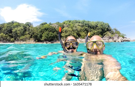 Young couple taking selfie in tropical scenario with waterproof camera - Boat trip snorkeling excursion at Similan islands - Youth lifestyle and travel concept around world - Bright vivid filter