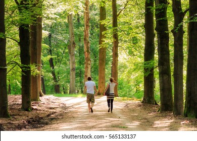 Young couple taking a spring walk in the forest in the Netherlands, with fresh green leafs and lots of warm sunshine