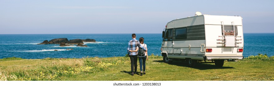 Young couple taking a walk near the coast with a camper in the background