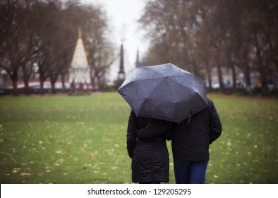 Young couple taking a walk in the park on a rainy day