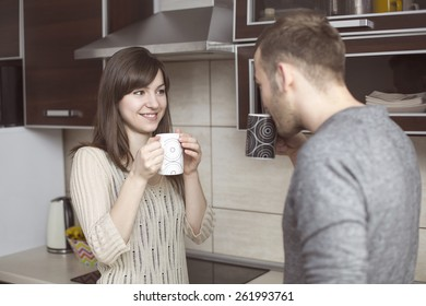 Young couple talking in kitchen with coffee