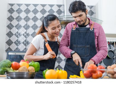 young couple is talking and smiling while cooking healthy food in kitchen at home.