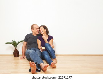 Young couple talking while sitting on the floor. Lots of copyspace.