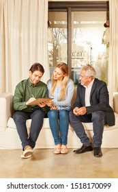 Young couple as a tenant or buyer together with the broker at the contract