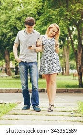 Young couple texting when walking in the park