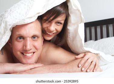 Young couple in their bed. They are playing in romance under the sheets.