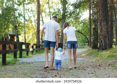 A young couple with their child in similar clothes white t-shirts and blue shorts is walking in the park. The view from the back. Warm summer sunny day. Young family