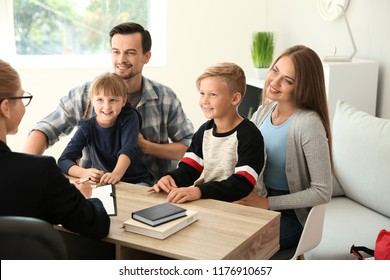 Young couple and their children meeting with headmistress at school