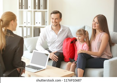 Young couple and their daughter meeting with headmistress at school