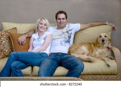 young couple with their dog sitting on couch