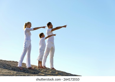 Young couple and their son, dressed in white, standing on top of a hill, pointing a direction.