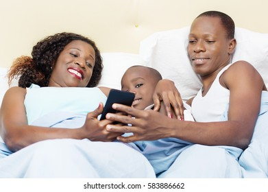 young couple and their son are happy to share the same mobile phone in bed
