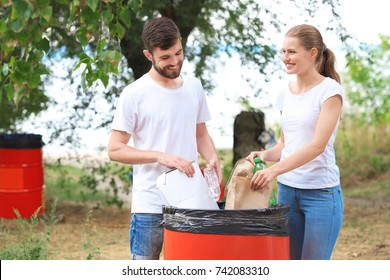 Young couple throwing garbage into litter bin outdoors