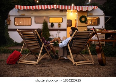 Young couple toasting with bottles of beer near trailer. Camping season