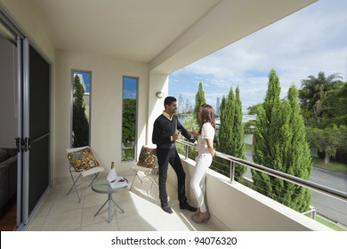 Young couple toasting with champagne on a modern backyard overlooking the city