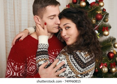 young couple together with christmas tree in home interior - love and holiday concept, xmas eve