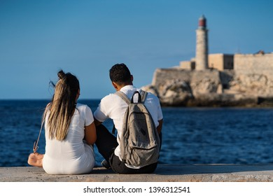Young couple together in Havana, Cuba. El Morro castle in the background.