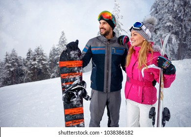 young couple together skiing on snowy mountain and looking something in distance