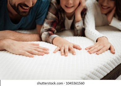 Young couple together with their young son test the material of the mattress for a touch. Family buys mattress in furniture store. Healthy posture concept.
