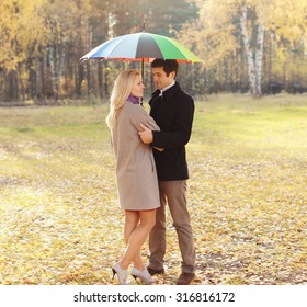 Young couple together with umbrella in autumn park