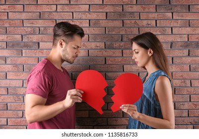 Young couple with torn paper heart near brick wall. Relationship problems