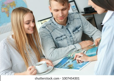 Young couple in a tour agency communication with a travel agent travelling concept booklet