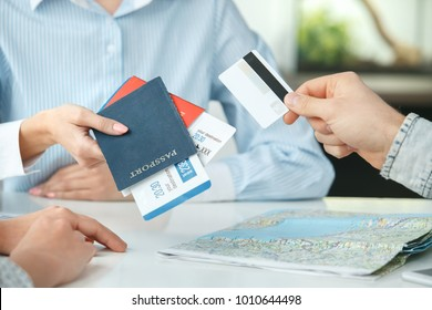 Young couple in a tour agency communication with a travel agent travelling concept credit card payment close-up