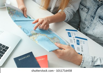 Young couple in a tour agency travelling concept choosing destination close-up