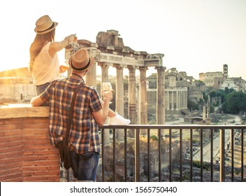 Young couple tourist with glass of white wine at Roman Forum at sunrise. Historical imperial Foro Romano in Rome, Italy from panoramic point of view.
