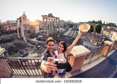 Junge Paare Tourist schauen auf das Forum Romanum bei Sonnenaufgang und Küssen Selbstdrehen. Historisches kaiserliches Foro Romano in Rom, Italien aus panoramischer Sicht.
