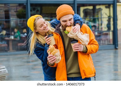 Young couple of tourists eating fastfood on city street outdoors. Blond woman feeding hungry beard man. People enjoying life walk down the city street. Food, adventure, traveling, lifestyle concept.
