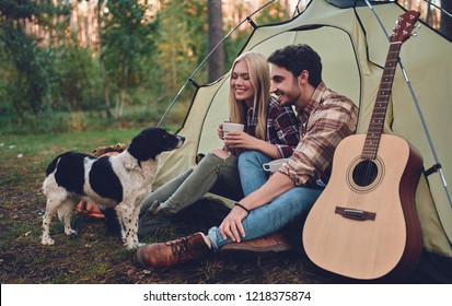 Young couple of tourists are exploring new places together. Attractive woman and handsome man are spending time together on nature with dog. Sitting in touristic tent in forest and drinking tea.