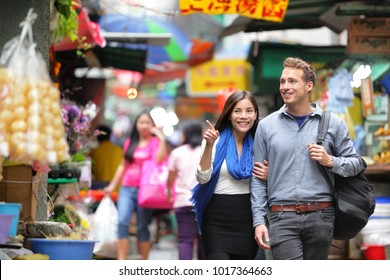 Young couple tourists walking shopping in street food market in Hong Kong. Couple looking around at stand shops. Asian woman, Caucasian man interracial people.