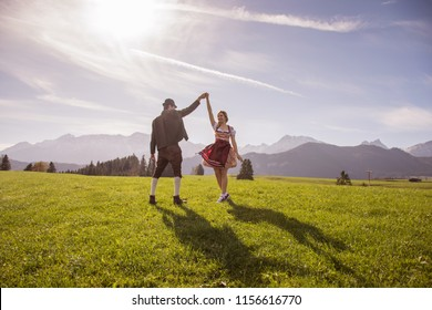 Young couple in traditional bavarian clothes with girl in dirdl dress dance in nature / Bavarian Couple Dance Oktoberfest Munich