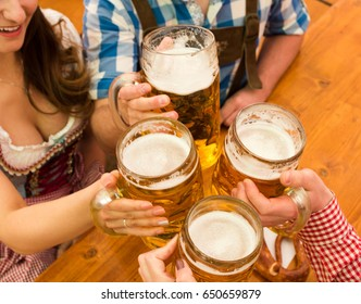 Young couple in traditional Bavarian Tracht - Dirndl and Lederhosen - in a beer tent at the Oktoberfest in Munich toasting with their 1 liter beer mugs