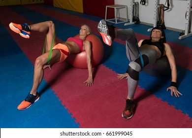 Young Couple Train Together With Resistance Bands On Ball - Leg Exercise In A Health And Fitness Concept