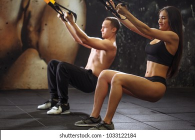 Young couple are training on trx. Total Body Resistance Exercises.